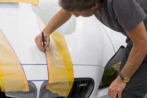 Fedeli alla maquette sviluppata  da Baldessari nel suo studio  di Santa Monica, lo staff applica e sagoma  sulla carrozzeria dell'auto le maschere.