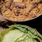 La lunga cottura con tutte le parti del maiale e la graduale aggiunta di foglie di verza.