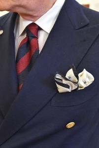 Blazer in shantung, cravatta regimental in grenadine e camicia in batista fantasia con colletto bianco.