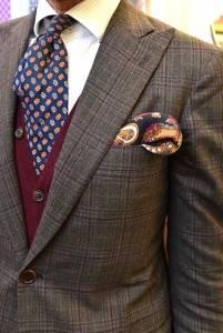 Giacca sportiva in tela di lana ritorta,  gilet di cashmere bordeaux, cravatta fantasia  e camicia a righine.