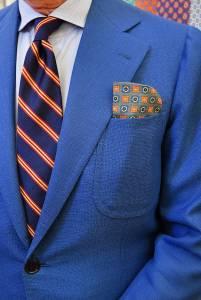 Monopetto in hopsack di lana con cravatta regimental in reps, camicia in Oxford celeste e portaocchiali in seta stampata nel taschino.