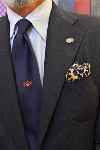 Completo formale in pettinato cable stripe, cravatta e spilla del Cavalleresco ordine, camicia mille righe e foulard femminile nel taschino.