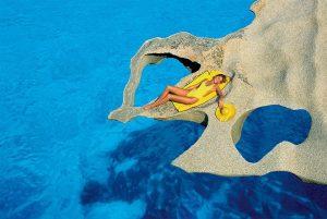 Una modella in posa su una roccia di granito in Gallura, nel nord della Sardegna; tra queste acque Curto, da bambino, ha indossato la sua prima maschera da sub cominciando a esplorare il mondo sottomarino.