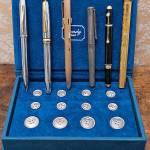 un set di bottoni d'argento con alcune penne: la prima è una Cross, la seconda una Montblanc, la terza una Papermate con disponibili diversi colori, l'ultima una Cartier
