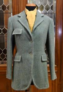 Una hacking jacket in harris tweed Lovat green. Grazie ad Alessandra Gallo, la sartoria produce anche capi femminili. L'originale impuntura a catenella è una citazione di Angelo Litrico.
