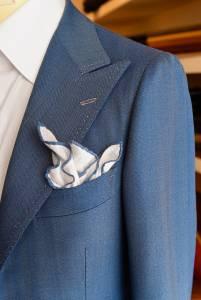 La parte alta del quarto anteriore di una giacca da mezzi tempi in solaro azzurro evidenzia la pulita attaccatura a camicia della manica e il vezzo partenopeo della doppia impuntura, specialmente sui tessuti leggeri.